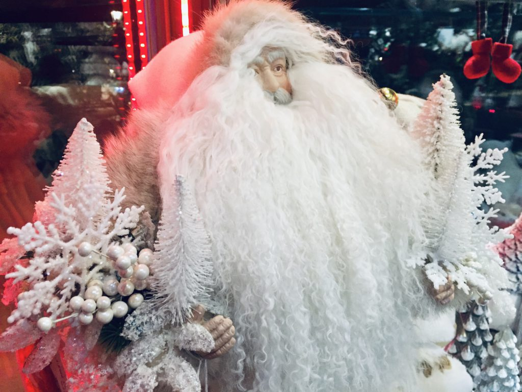 Father christmas with white pendelton coat and white beard, holding white christmas trees and snowflakes